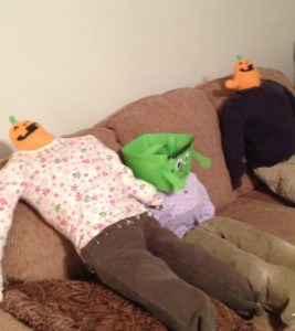 Two tiny pumpkin head scarecrows share a laugh with a monster head scarecrow